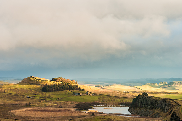 image of Steel Rigg and Hadrian's Wall bathed in late golden sunshine after a rain shower
