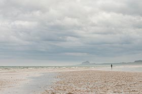 image of Bamburgh castle and a lone person from Ross Sands